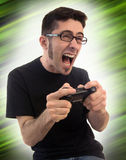 Excited man playing video games. A young adult male on a funky green background getting pretty excited and upset about his video games Royalty Free Stock Images