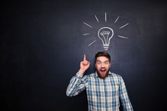 Excited man pointing up over blackboard background with light bulb. Excited bearded young man in checkered shirt pointing up over blackboard background with Royalty Free Stock Photography