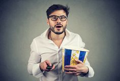 Excited man with popcorn watching TV. Handsome bearded man in glasses holding bucket of popcorn and remote watching TV with amazement Royalty Free Stock Photography