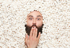 Excited man in popcorn. Young man looking shocked covering mouth with while lying in popcorn Stock Photos