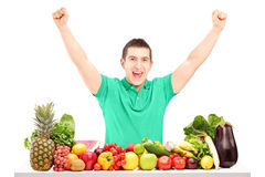 Excited man raising hands and posing with a pile of fruit Stock Photos