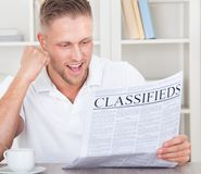 Excited man reading the classifieds cheering Royalty Free Stock Photos