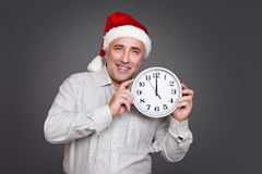 Excited man with santa hat holding clock Royalty Free Stock Images