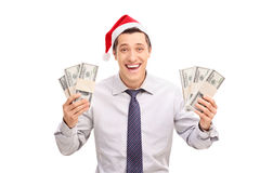 Excited man with Santa hat holding money. Excited young man with Santa hat holding a few stacks of money and looking at the camera isolated on white background Royalty Free Stock Image