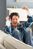 Excited Man Sitting On Sofa At Home On Phone Stock Photos