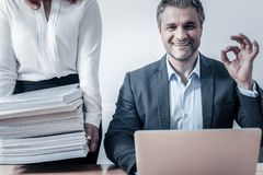 Excited man smiling after checking pile of documents. The work is done. Radiant entrepreneur showing ok sign and grinning broadly into the camera after working Royalty Free Stock Photos