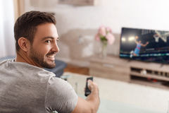 Excited man switch TV to basketball. By remote control Royalty Free Stock Photography