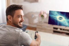 Excited man switch TV to sci-fi movie. By remote control Stock Images