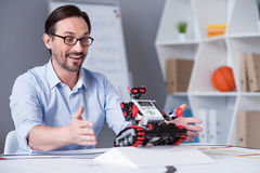 Excited man testing a little red robot Stock Image