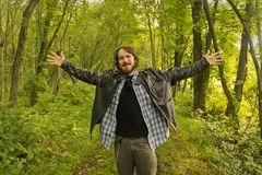 Excited Man Trail. An excited city slicker spreads arms while wandering along a trail in the woods Stock Photo
