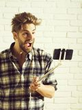 Excited man uses selfie stick. Excited handsome man young blond bearded male model with beard in plaid shirt uses smartphone or mobile phone on selfie stick on royalty free stock photography