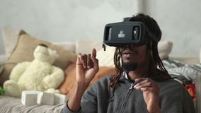 Excited man using virtual reality goggles at home. Excited african american man with dreadlocks sitting on the floor and using VR headset glasses. Hipster in stock footage