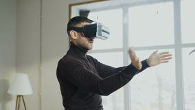 Excited man with virtual reality headset playing 360 video game at home stock video