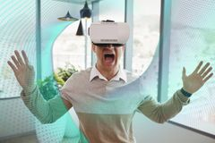 Excited man in VR headset looking at interface. Digital composite of Excited man in VR headset looking at interface Royalty Free Stock Photo