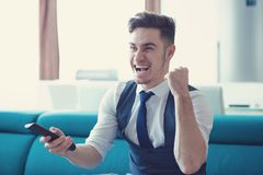 Excited man watching news on TV. Young cheerful man watching game with remote sitting on sofa and looking thrilled Stock Image