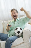 Excited Man Watching Soccer Match On Sofa Royalty Free Stock Photos