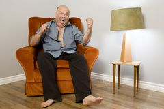 Excited Man Watching Sports. A mature aged man sitting in a lounge chair with an excited demeanor, perhaps winning the lottery or focused on sports stock photography