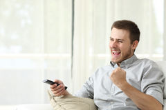 Excited man watching tv Stock Photo