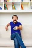 Excited man watching tv. And holding control panel Royalty Free Stock Image