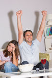 Excited man watching TV with wine and popcorn by bored woman at home Royalty Free Stock Image