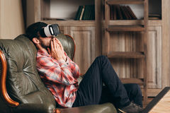 Excited man watching video in vr glasses. Young bearded male watching emotional movie in virtual reality headset, feeling shocked and thrilled. Cinema at home Stock Photos