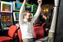 Excited man winning in a slot machine. Good looking men looking happy and excited about hitting the jackpot in a slot machine at a casino Royalty Free Stock Image