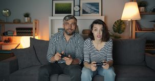 Excited man and woman playing video game in dark apartment having fun. Together enjoying leisure time and modern devices. People and entertainment concept stock footage