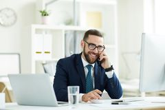 Excited manager talking on phone. Cheerful excited young bearded manager in eyeglasses sitting at desk with modern computers and talking on mobile phone stock image