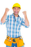 Excited manual worker clenching fists. Portrait of excited manual worker clenching fists on white background Royalty Free Stock Photography