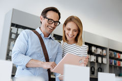 Excited married couple using template digital tablet at electronics store royalty free stock photos