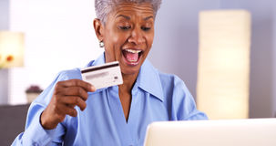 Excited Mature African woman buying things online Royalty Free Stock Images