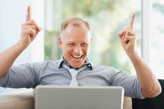 Excited mature business man using a laptop at work Royalty Free Stock Photos