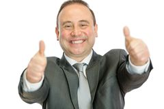 Excited mature businessman giving thumbs up signal stock image