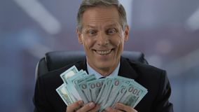 Excited mature businessman holding dollar banknotes in hands, company income stock video footage