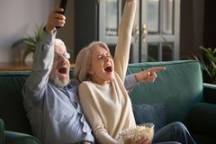 Excited mature couple, man and woman watching football, celebrating victory stock images