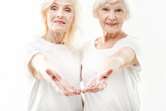 Excited mature ladies inviting someone by gesture. Join to our healthy team. Friendly old women are stretching arms to camera with invitation. They are embracing royalty free stock image