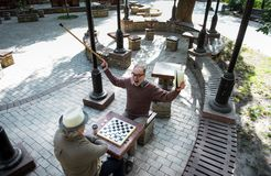 Excited mature male pensioner winning his opponent in draughts Royalty Free Stock Photo