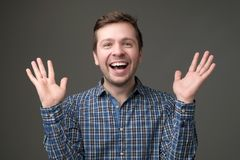 Excited mature man standing with raised hands and looking at camera. stock image