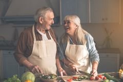 Excited mature pensioners preparing dinner together