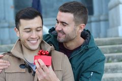 Excited man giving a present to his loved one with copy space. Excited men giving a present to his loved one with copy space Stock Photography