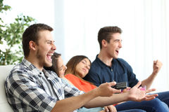 Excited men watching tv and bored girlfriends. Sitting on a couch in the living room at home Stock Image