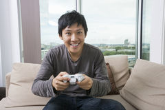 Excited mid adult man playing video game on sofa Stock Image