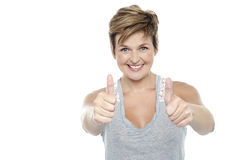 Excited middle aged lady showing double thumbs up. Excited middle aged lady standing in front of camera and showing double thumbs up sign Royalty Free Stock Photography