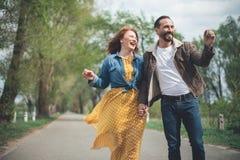 Joyful mature loving couple walking along park alley stock photos