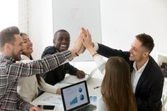 Excited millennial group giving high five for result achievement. Excited diverse millennial group giving high five celebrating online business win or shared stock image