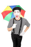 Excited mime artist holding a colorful umbrella Stock Photography