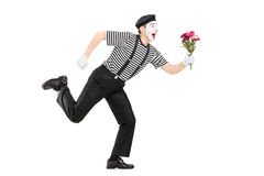 Excited mime artist running with a bouquet of flowers Royalty Free Stock Photos