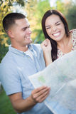 Excited Mixed Race Couple Looking Over Map Outside Together Royalty Free Stock Images