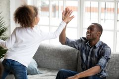 Excited mixed race daughter give high five to young dad royalty free stock image