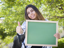 Excited Mixed Race Female Student Holding Blank Chalkboard Stock Photography